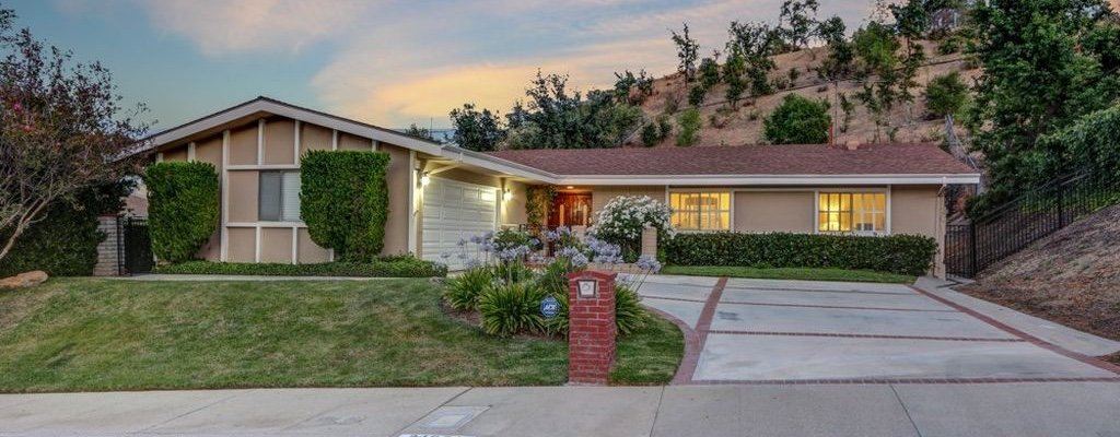 A picture of a modestly sized house with a tan roof and tan exterior paint with the lights on inside, and sitting on the side of a hill in Los Angeles, CA.