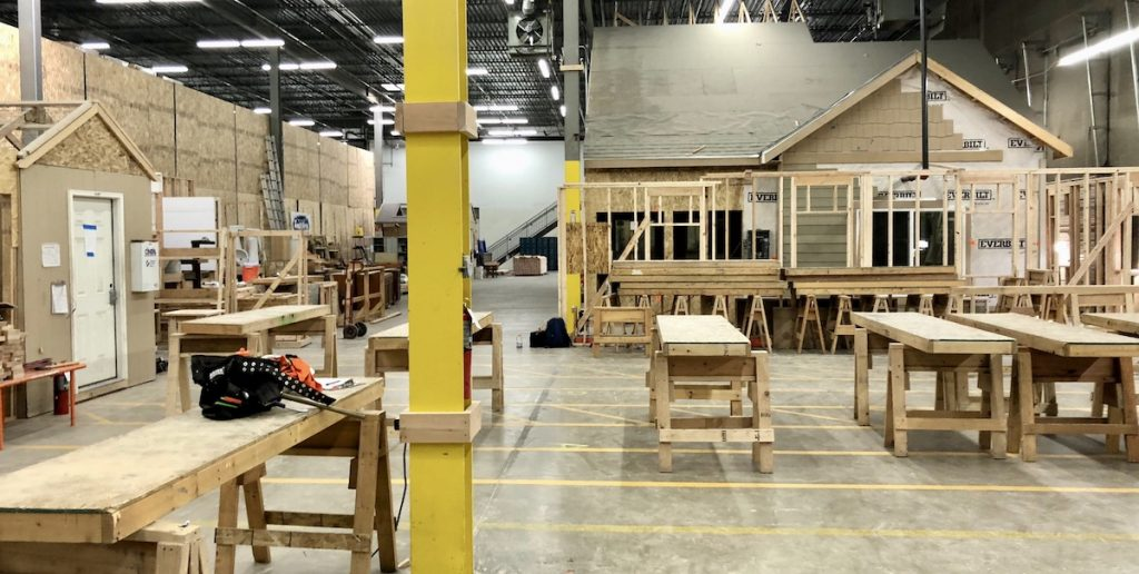 The inside classroom showing a house half built with workbenches around it in the Colorado Homebuilding Academy.