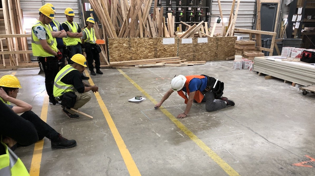 The instructor teaching us about angles used in framing, using chalk on the warehouse floor of the Colorado Homebuilding Academy.