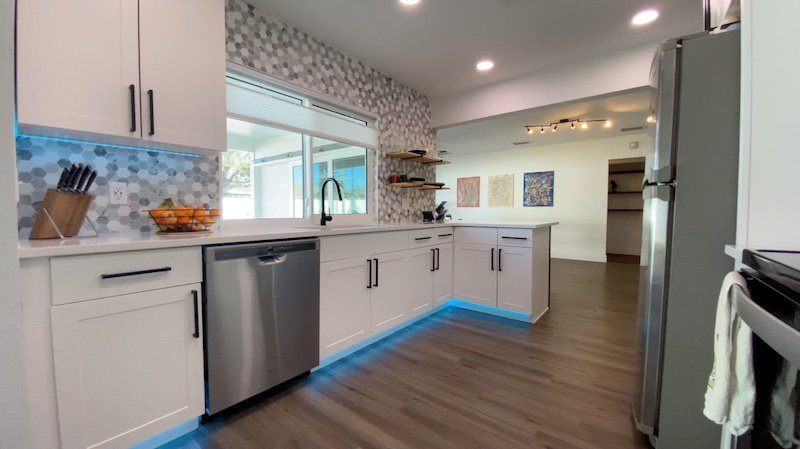 A picture of the kitchen finished in our first net-zero home renovation. It shows greyish brown floors, white cabinets, and colorful LED lighting in a well-lit room.