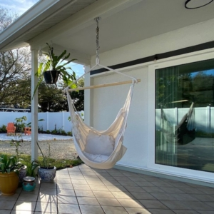 A picture of the background in our first net-zero home renovation, showing brand new impact sliding doors installed with a hanging chair next to it.