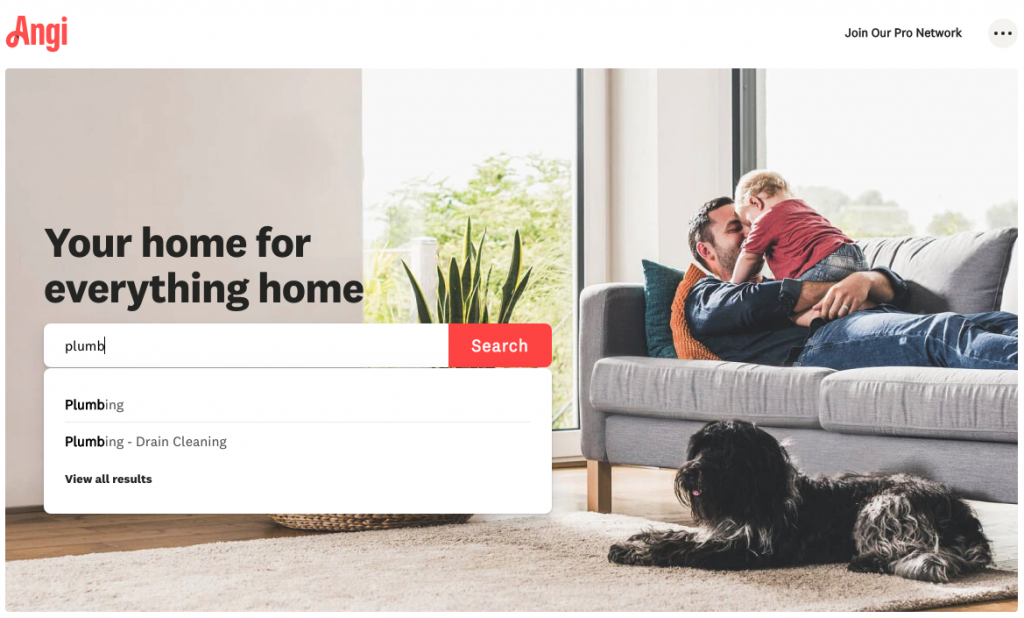 A screenshot of the Angi homepage, showing a search bar on the left side, a picture of a man with his child on a grey couch.