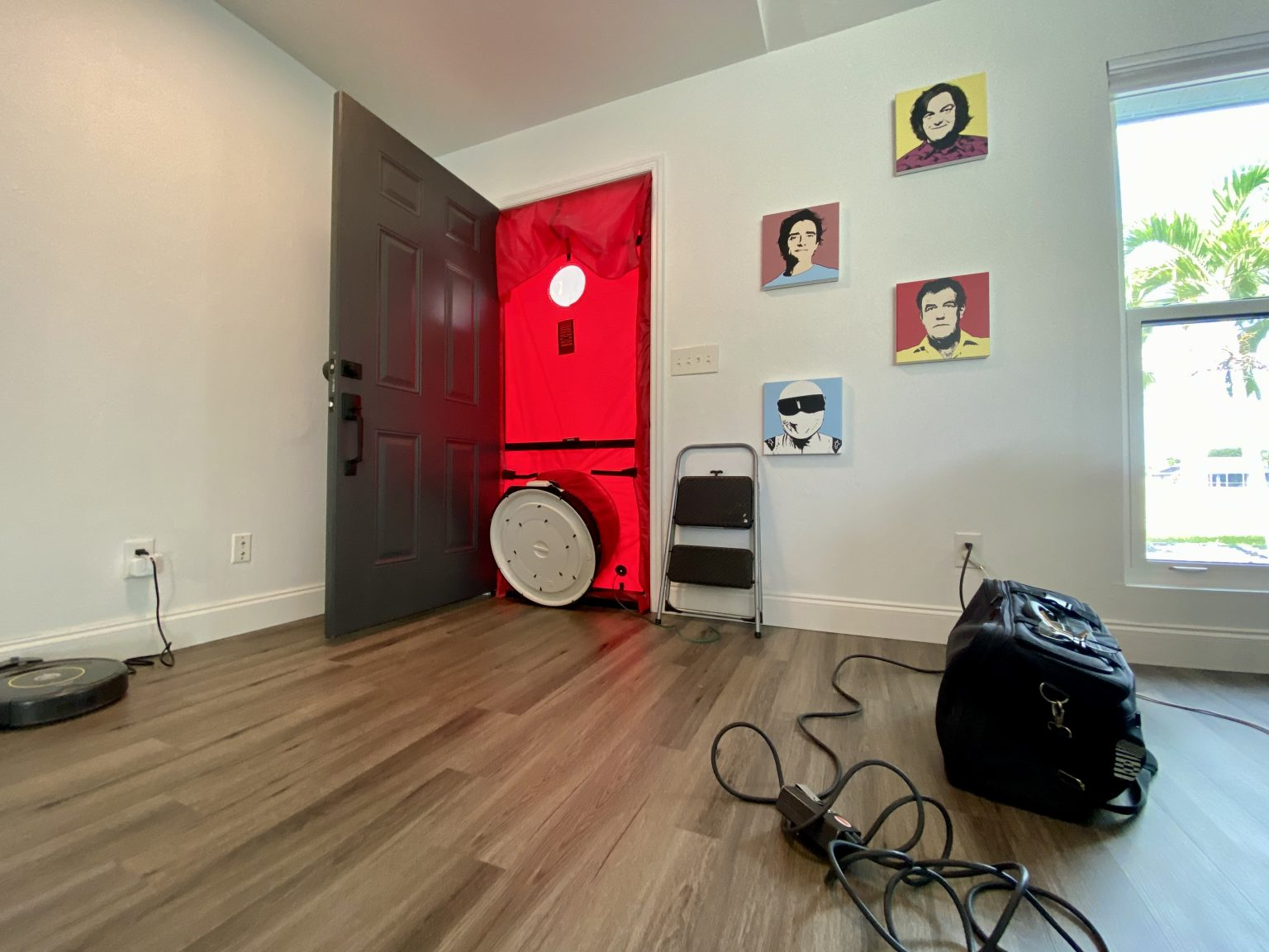 A picture of the doorway with a blower door test attached in our attainable net zero energy solar home. The door is opened with the testing machine creating an airtight seal and a fan inside it.