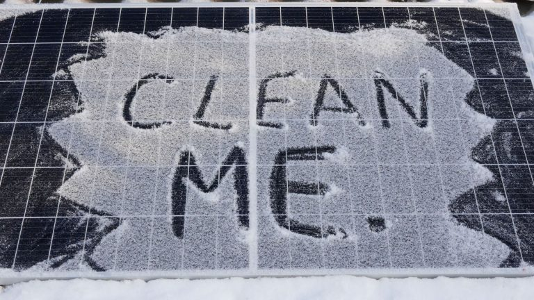"A picture of two solar panels together with light snow covering them. Written in the snow is ""clean me"", indicating the need to brush off the snow."