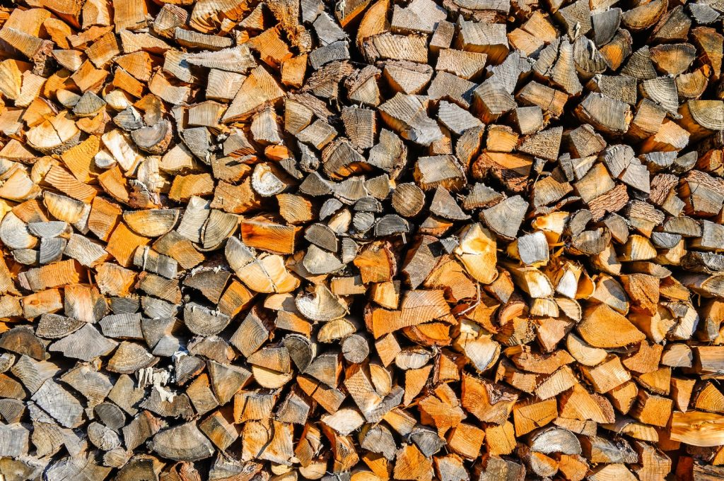 A picture of chopped-up trees in block forms for use in biomass fuel applications. The wood is older and has a lot of orange and grey colors to it as it sits in the pile.