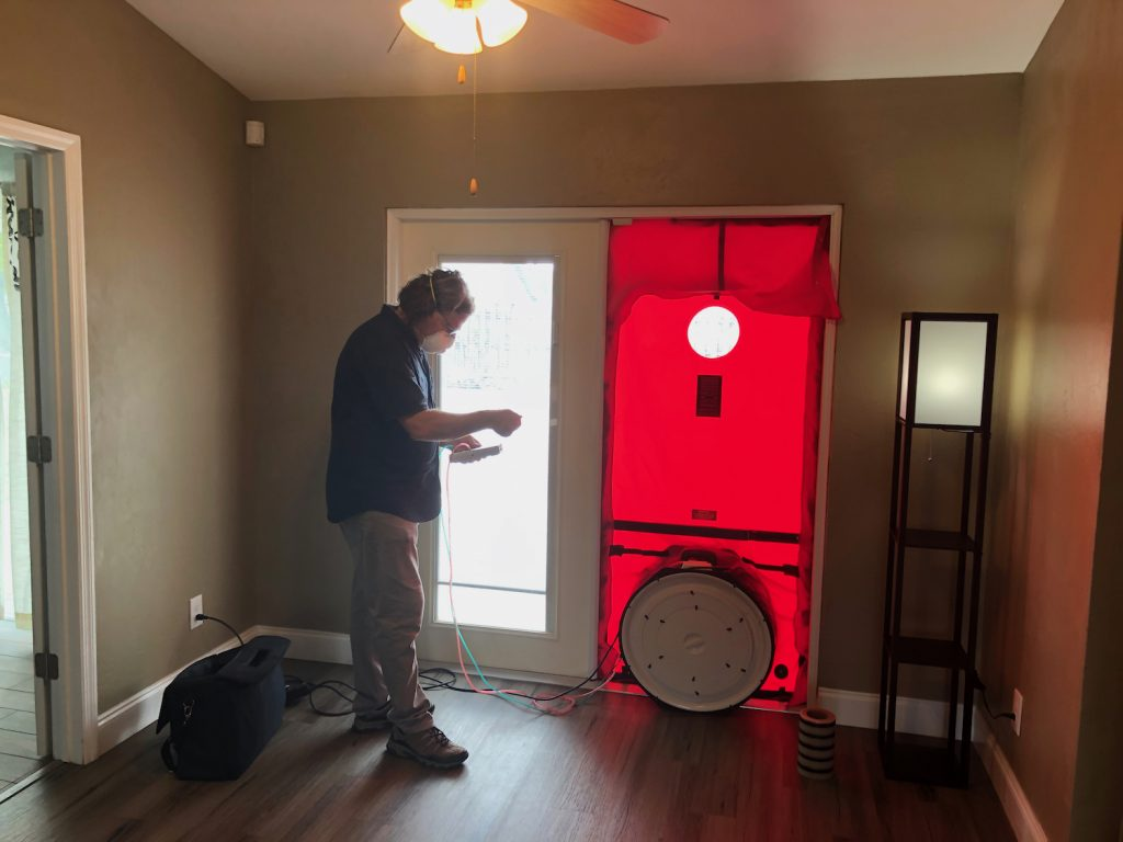 A man standing near the doorway with a blower door test installed. The main is reading the measurements so we can look at the benefits of blower door test.