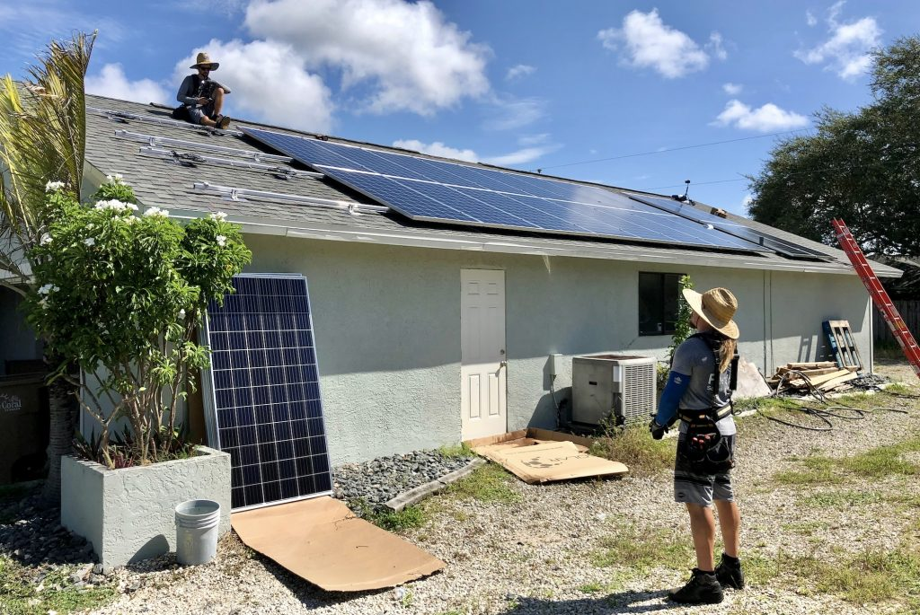 A picture of a man on the ground speaking with a man on the roof installing solar energy on a teal house. This is part of our net-zero home renovation project.