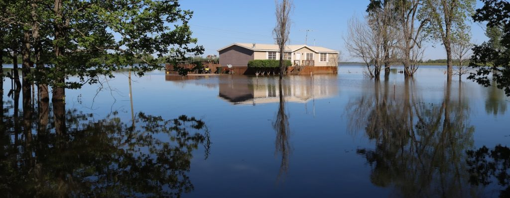 A picture of a small home surrounded by flooding.