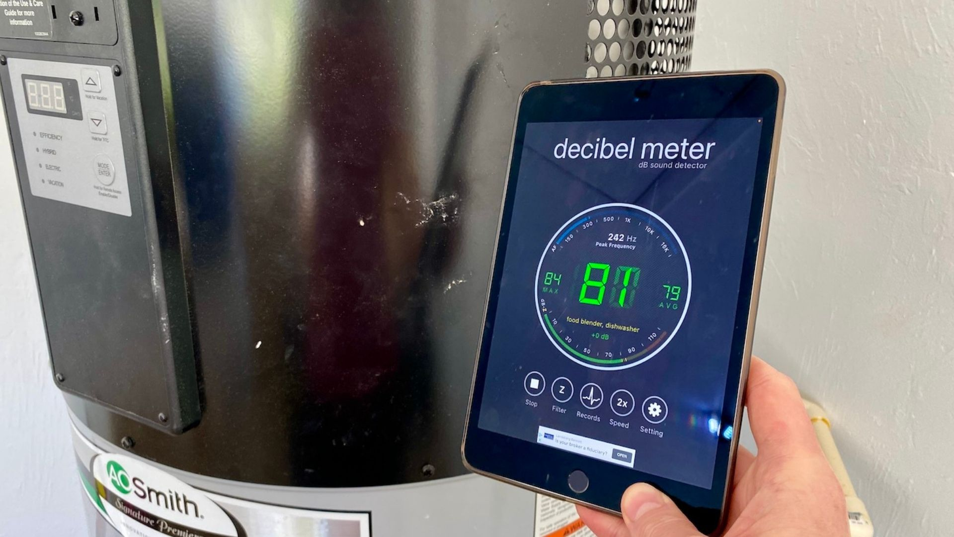 A picture of our hybrid heat pump hot water heater in the background, with me holding up an iPad. The screen shows a decibel level reading of 81, indicating how loud this hot water heater is.