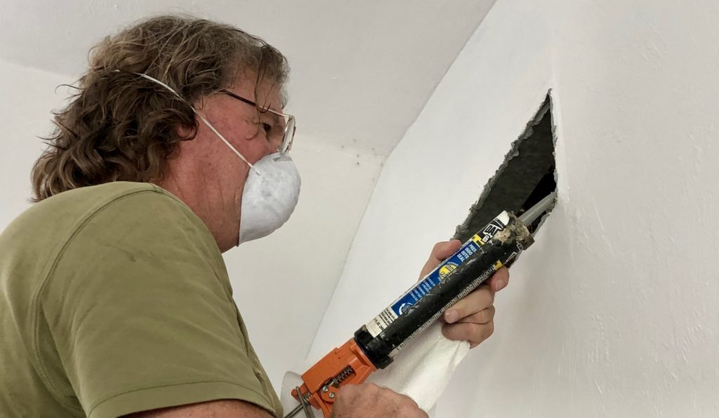 A picture of a man using regular caulk to seal the gaps around a rectangular air vent in the wall inside of our net-zero home renovation.