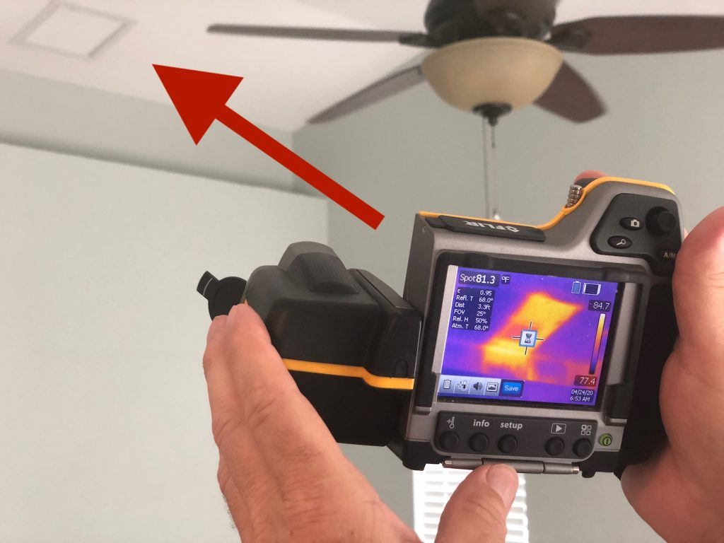 Shows an infrared camera with yellow areas on the screen, showing higher heat infrared readings on the HVAC duct return vent in our net-zero home.
