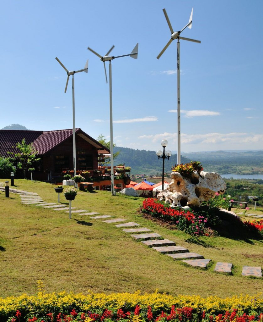 A picture of a house on a hill with three small residential wind turbines. There is a walking path around the turbines with flower beds spread out.