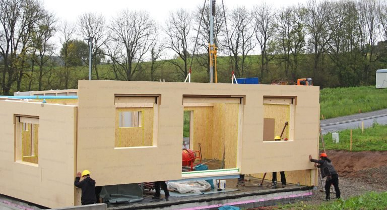 A picture of a small prefabricated home being built. It shows unpainted walls hanging from a crane being moved into place with the help of two construction workers.