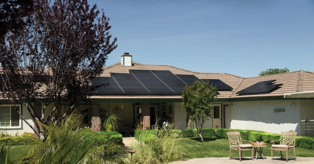 A picture of a tan-colored home with some black solar panels on the tile roof, with some nice landscaping around, including a patio set of tables and chairs.