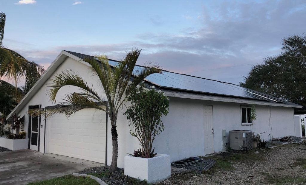 A picture of our net-zero solar home renovation project in Cape Coral, FL. It shows the exterior of the white-painted home with dark blue solar panels during a sunset.