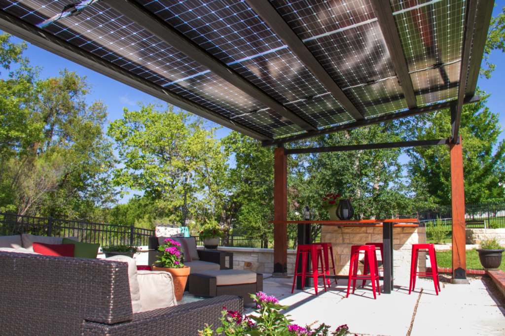 A picture of a really nice back yard featuring a patio set and solar panels mounted as a shade structure above the grill.