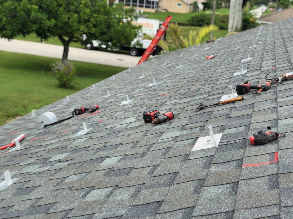 A picture of our roof during the solar energy installation. It shows many roof penetrations from the solar racking mounting system hardware going into the roof over the shingles