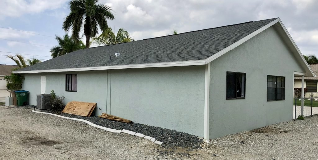 A picture of a teal-colored house exterior with a dark grey roof. This is the before picture of the net-zero home renovation we completed.