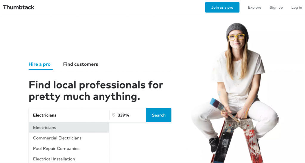 A picture of Thumbtack's homepage, showing the top menu, a search bar displaying local electricians, and a girl sitting on top of a ladder covered in pain from her painting project.