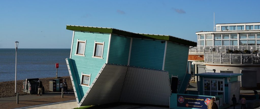 A picture of a teal green colored home sitting upside down near a beach. Representing what homeowners might feel like when investors take advantage of them as described in the John Oliver Mobile Homes Episode.