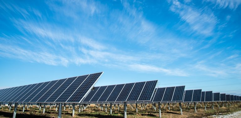 A picture of a large utility-level solar array with solar panels mounted on the ground, and a bright sunny sky in the background.