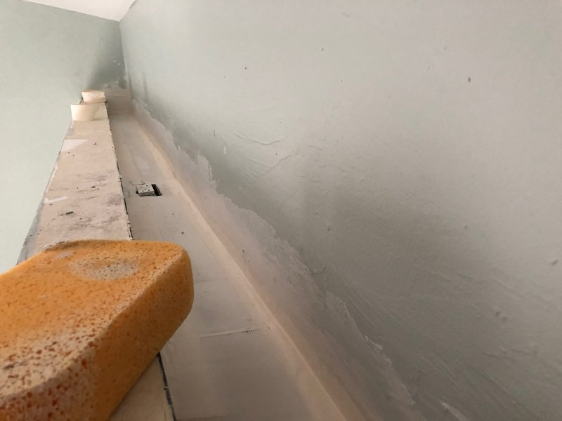 A picture of a soffit or shelf towards the ceiling in our master bedroom. It shows drywall plaster and a sponge, and the shelf being totally air-sealed for energy efficiency.