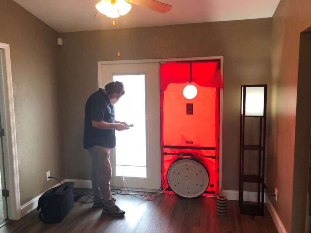 technician performing a blower door test to find air leaks