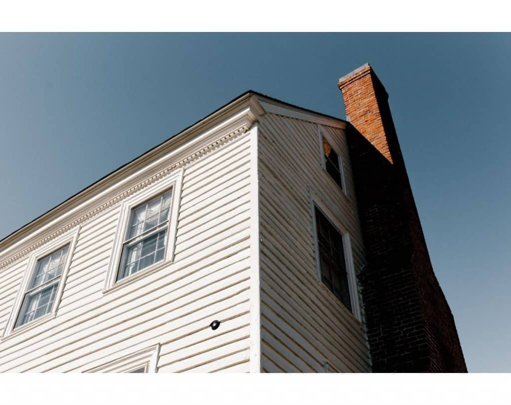 view of a white house with a red brick chimney