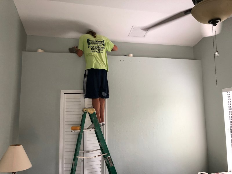 Our drywall contractor is standing on a 6ft ladder with a neon green shirt, drywalling the air gaps in our master bedroom.