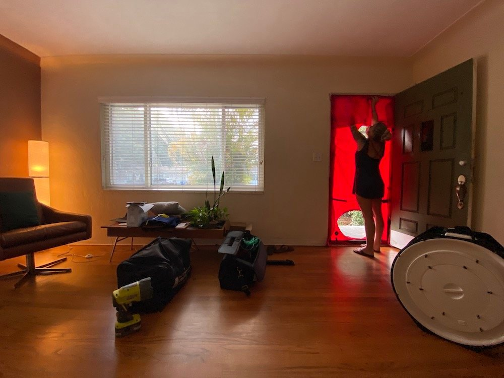 A woman is installing the red fabric part of a blower door test in the doorway of a living room.