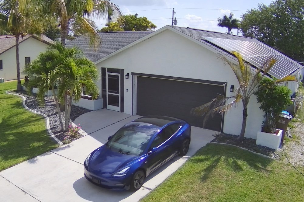 A picture of a blue Tesla Model 3 in front of our white-painted net-zero house with solar panels on the roof, and palm trees around the yard.