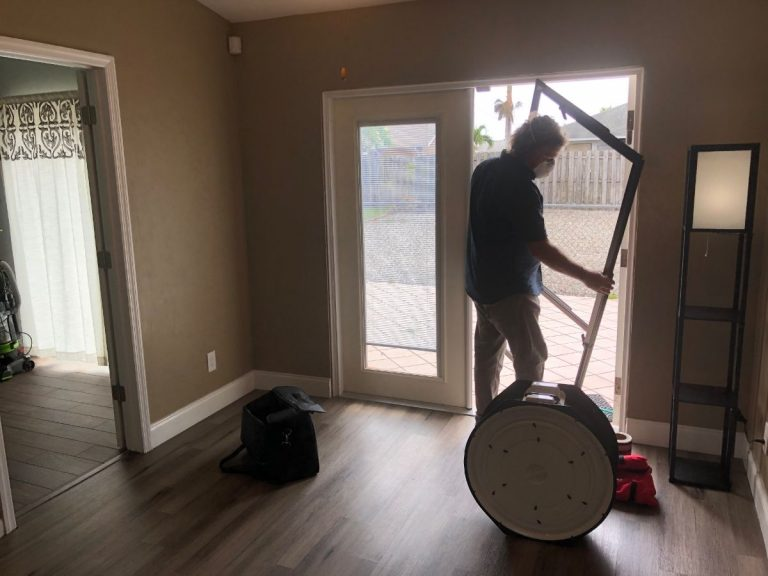 Photo of an energy auditor removing an exterior door from our first net-zero home in preparation to perform a blower door test.