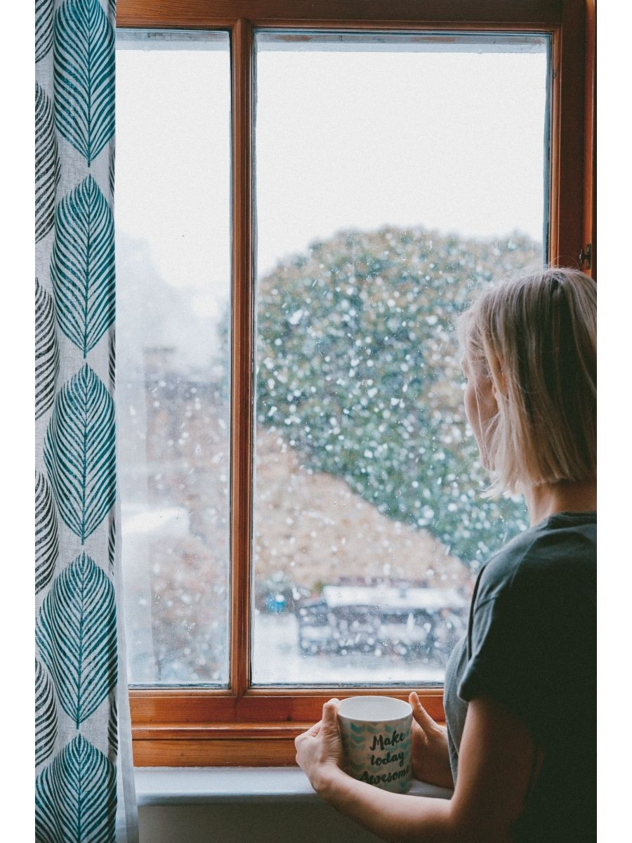 Photo of a woman in shirt sleeves holding a mug of tea looking out the window of a house at snow falling