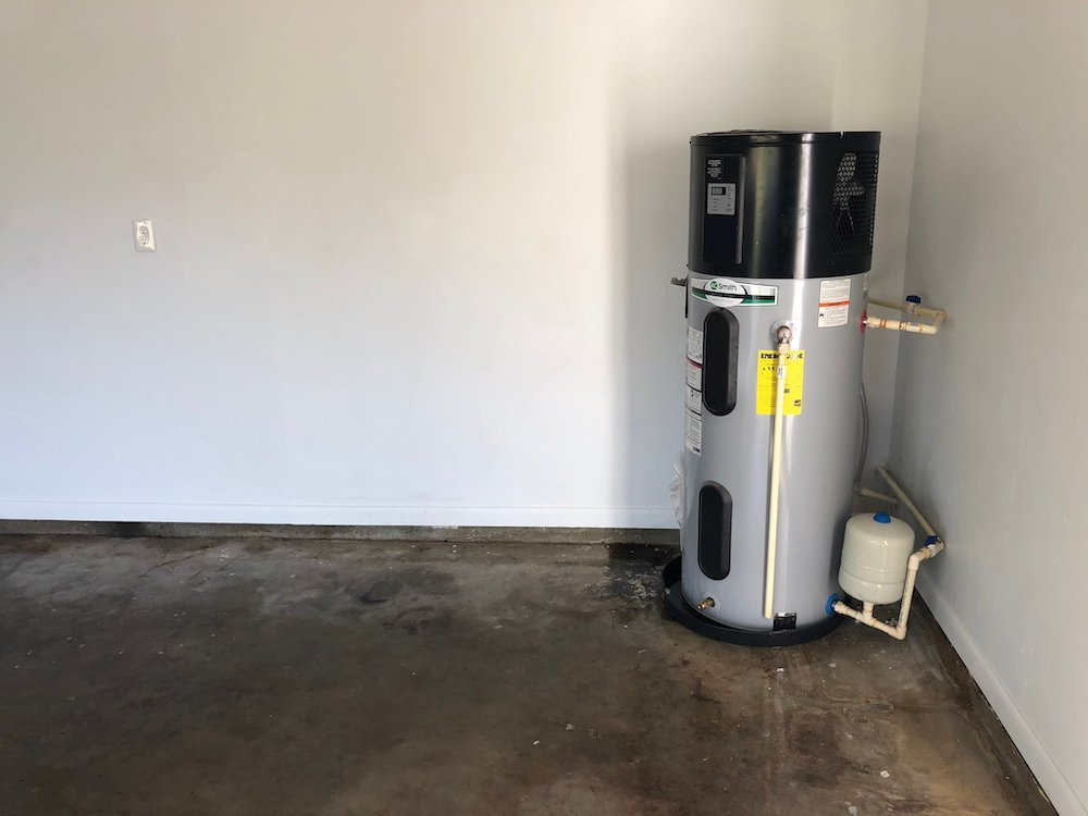 A picture of a hybrid heat pump hot water heater in an empty Florida garage.