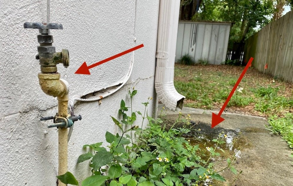 An outdoor water faucet leaking and creating a puddle on the side of the house, indicating phantom leakage and a higher water bill.