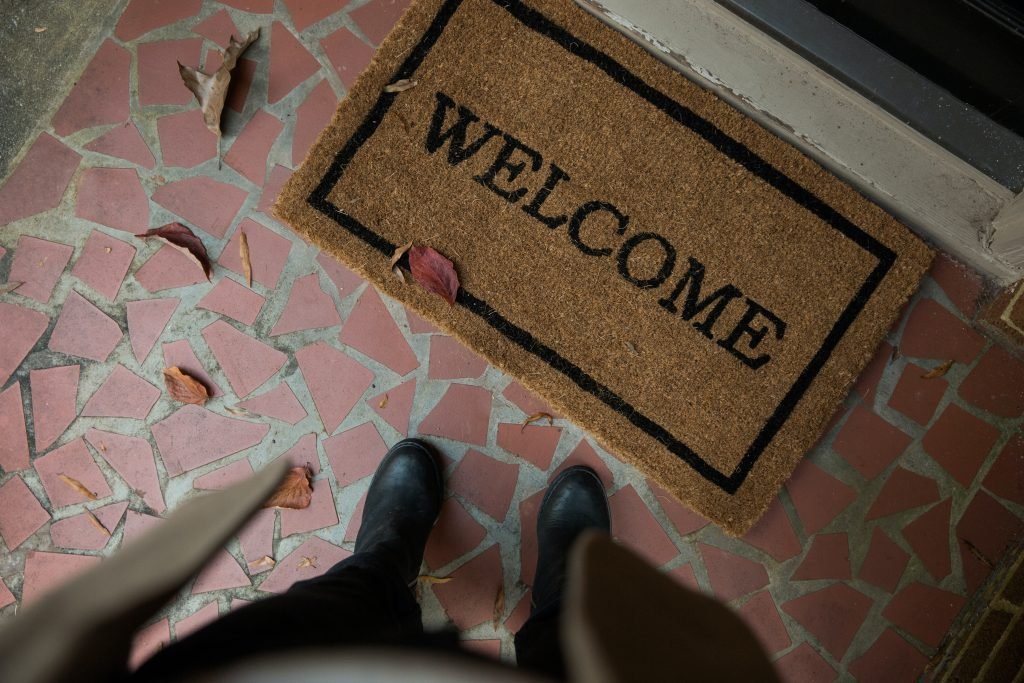 Photo of a person standing in front of a welcome mat to wipe the dust off their shoes