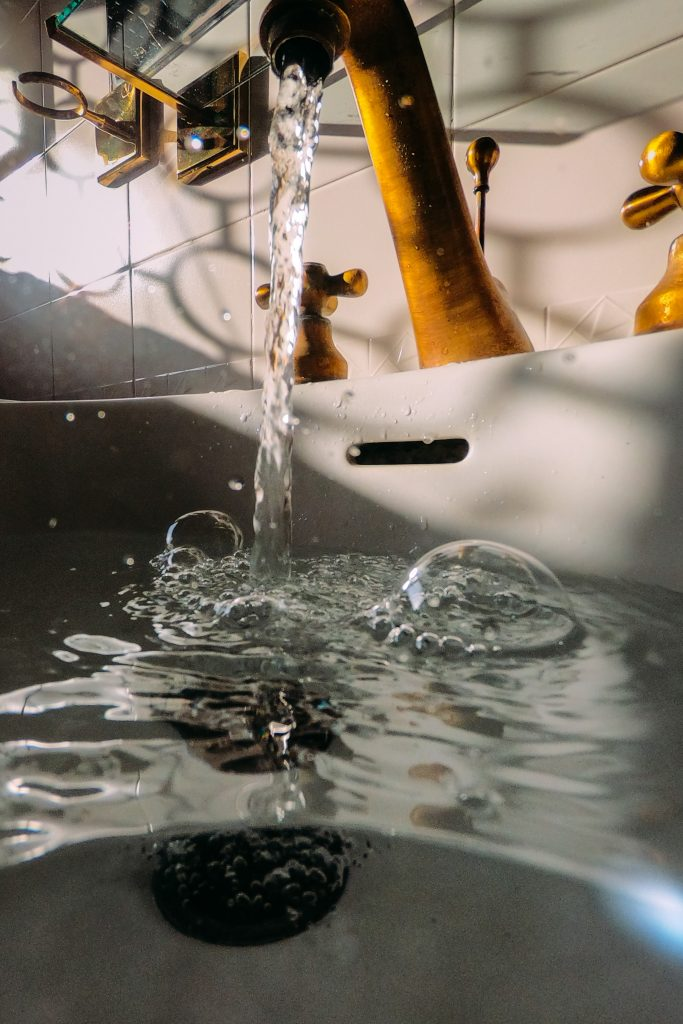 Photo of a household faucet running water into a sink with bubbles.
