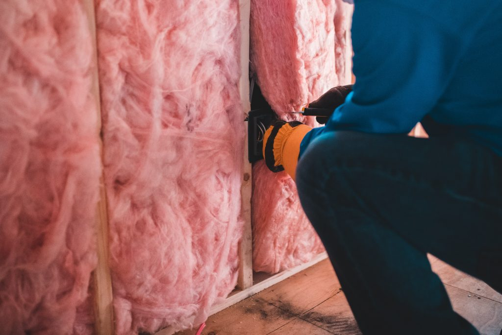 photo of pink fiber insulation being installed between wall studs in a house