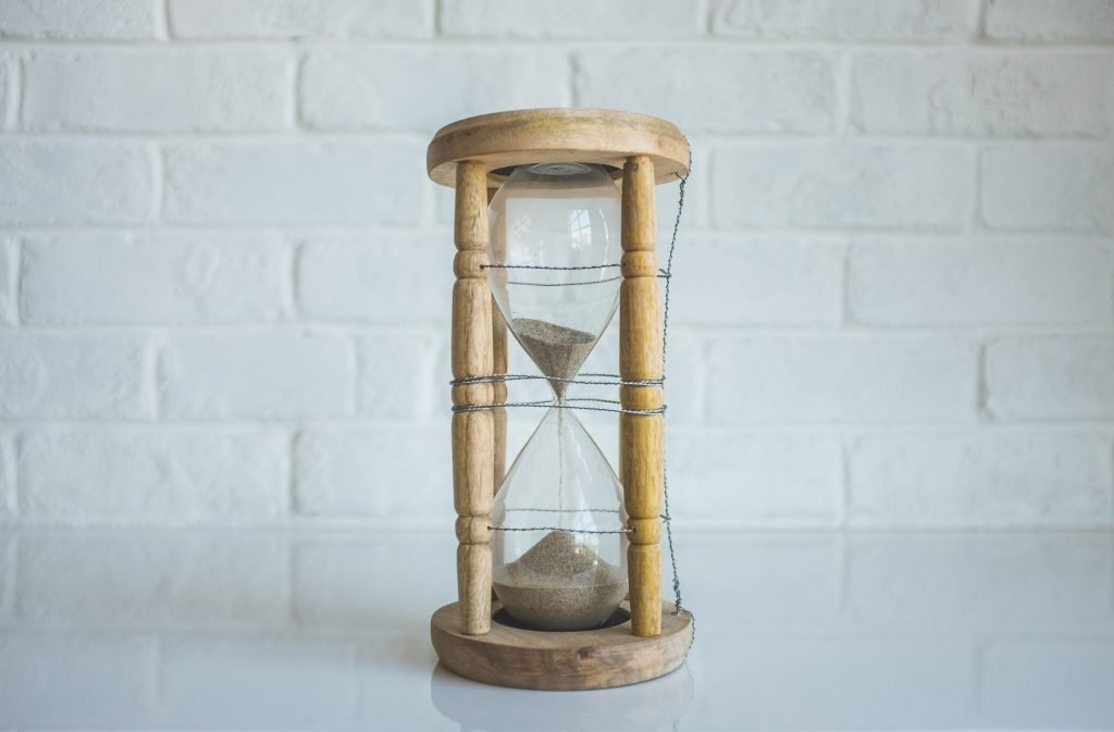 Picture of sand running through an hourglass on a white tabletop in front of a white brick background.