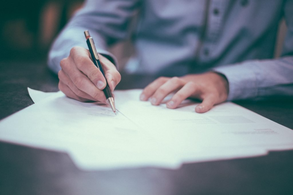 Photo of hands holding a pen, reviewing a document on a table top.