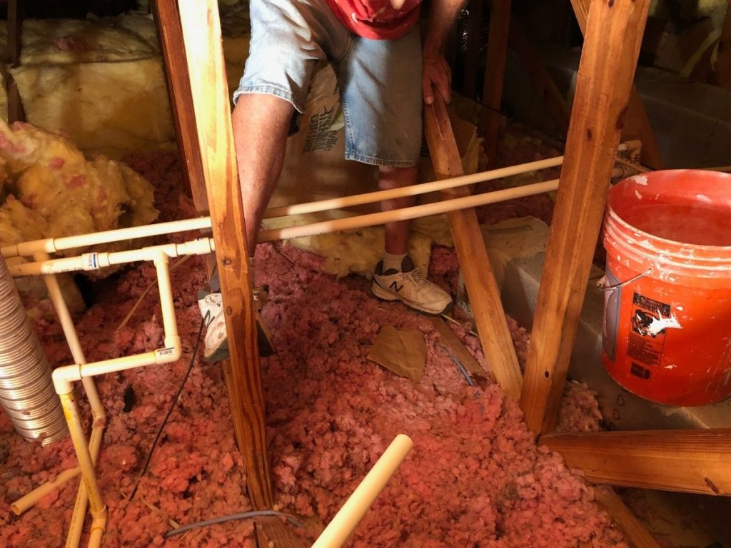 Picture of the attic floor in our first net-zero project home in Florida, covered in pink fiberglass insulation--better than nothing, but not as energy-efficient as it could be.