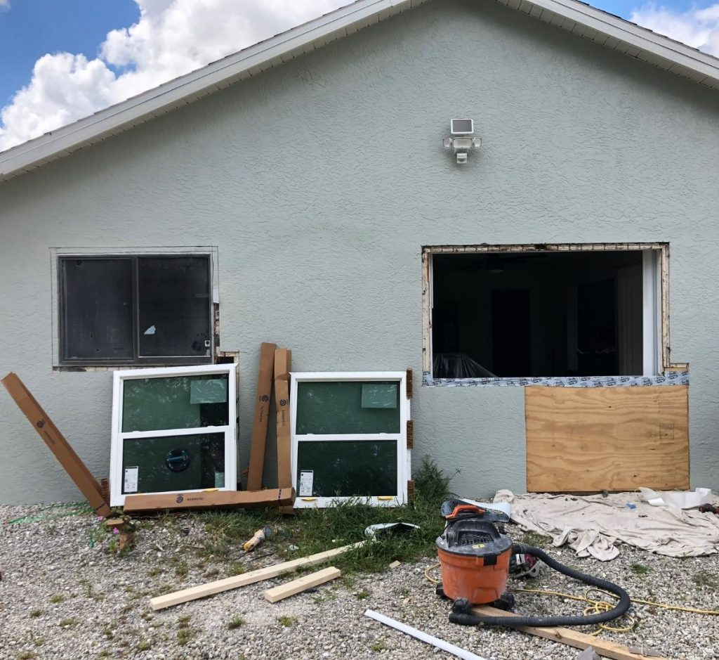 Photo of our first net-zero project house in the process of having windows replaced. One large window opening is empty and the new, energy-efficient windows are resting on the ground in front of the house.