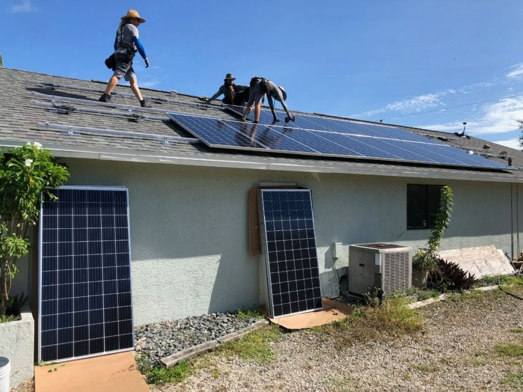 Photo of solar technicians installing solar panels on the roof of our energy-efficient net-zero renovation house in Florida, with extra panels resting against the side of the house.