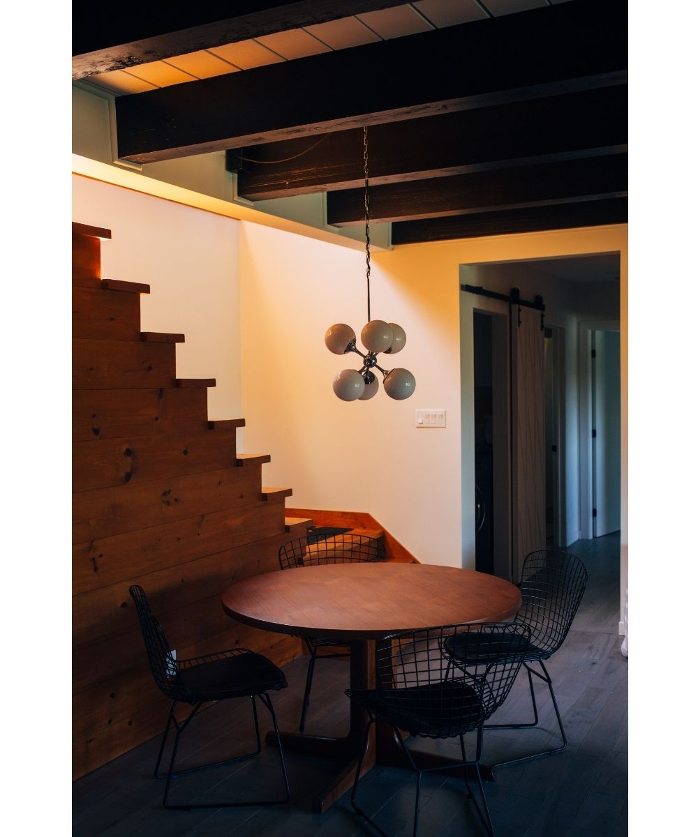 Photo of a finished basement with wooden stairs and a modern table, chairs and light fixture.