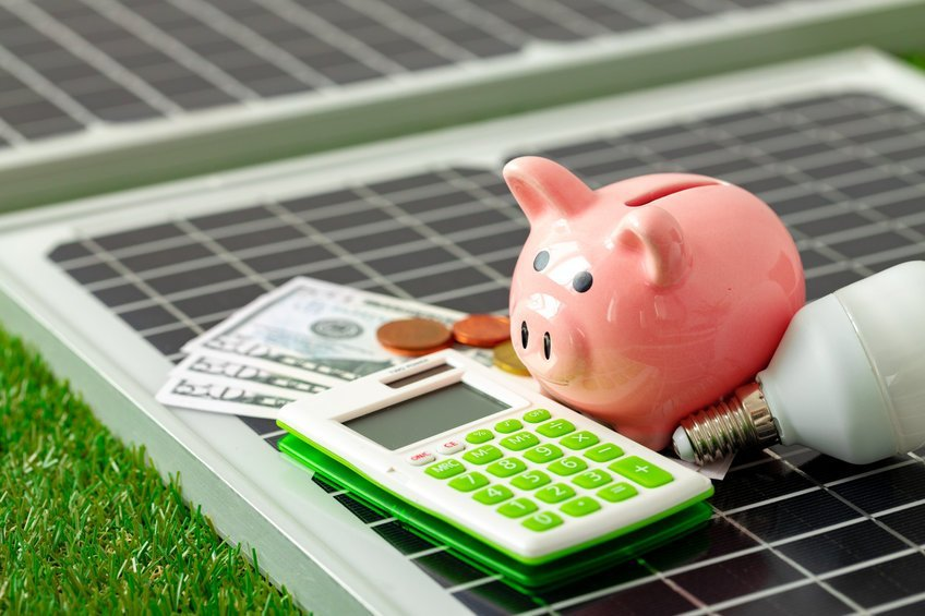 A picture of a calculator, some 50 dollar bills, a piggy bank, and a light bulb on top of a solar panel.