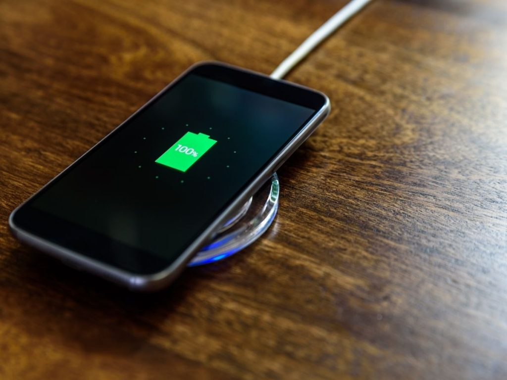 Photo of a cell phone plugged in laying on a wooden tabletop with a green fully-charged icon on its screen.