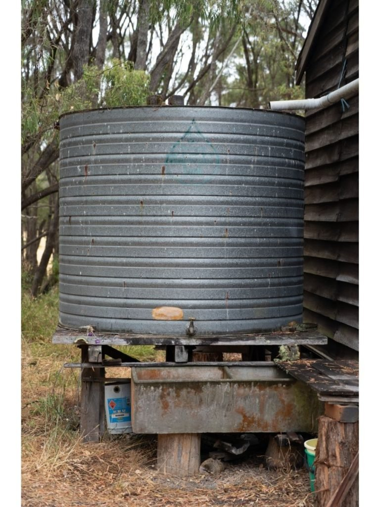 A large galvanized rainwater collection tank with a white PVC pipe from the roof positioned to drain into it sits outside a cabin in Australia with eucalyptus trees in the background