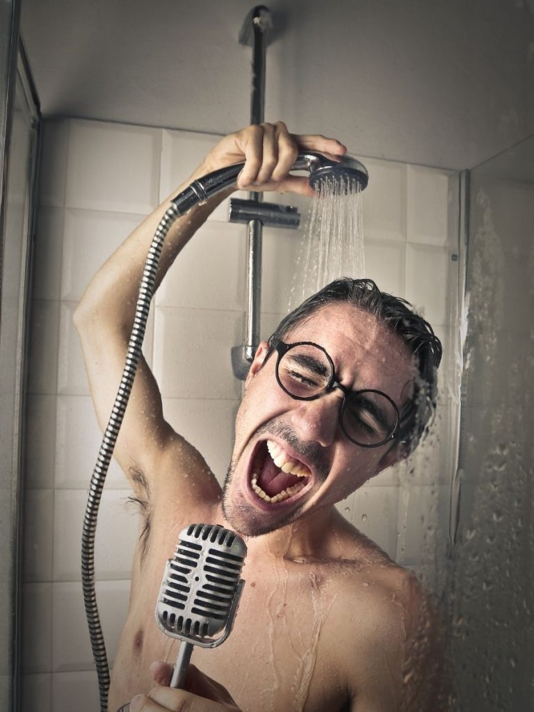 Photo of a person in the shower with a handheld shower head in one hand and an old fashioned microphone in the other, singing enthusiastically.