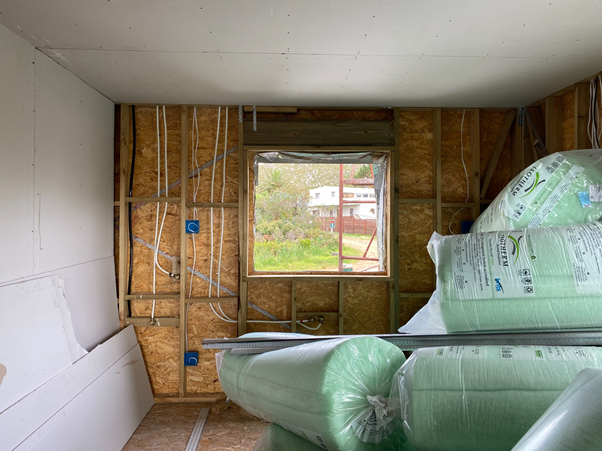 A 2x4 wood-frame wall with OSB sheathing. Electric cables and plumbing pipes for the kitchen in place and reflective insulation is used around the window. Rolls of eco-friendly thermally-bonded polyester PET are ready to be installed in the walls before the internal dry-wall gypsum board is fitted.
