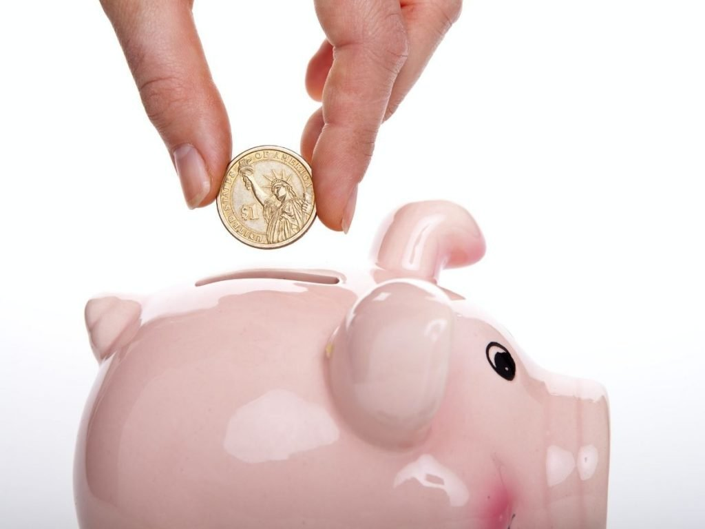Picture of a hand dropping a coin into a pink ceramic piggy bank.